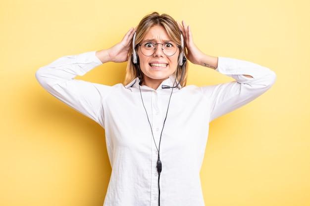 Ładna blondynka czuje się zestresowana, niespokojna lub przestraszona, z rękami na głowie. koncepcja zestawu słuchawkowego
