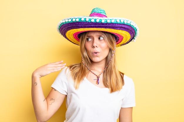 Ładna blondynka czuje się zestresowana, niespokojna, zmęczona i sfrustrowana. koncepcja meksykańskiego kapelusza