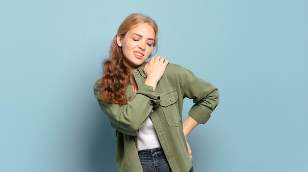 Ładna blondynka czuje się zmęczona, zestresowana, niespokojna, sfrustrowana i przygnębiona, cierpi z powodu bólu pleców lub karku