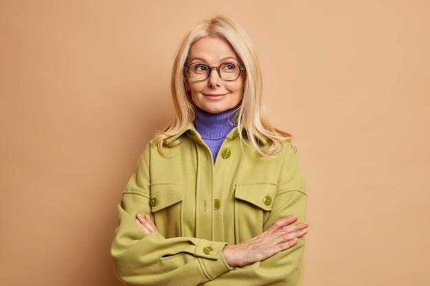 Ładna blondynka europejka o rozmarzonym wyrazie twarzy trzyma założone ramiona i wygląda w zamyśleniu na bok