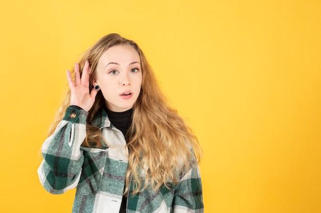 Ładna blondynka kaukaska, dłoń na uchu, słuchanie, żółte tło, miejsce