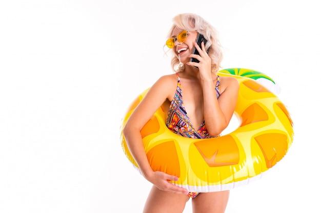 Ładna blondynka kaukaska kobieta stoi w stroju kąpielowym z gumowym pierścieniem plaży ananasa, rozmawia przez telefon z przyjaciółmi lub rodziną i uśmiecha się na białym tle