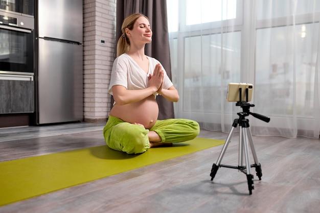 Ładna blondynka kaukaska kobieta w ciąży ćwiczy jogę, oglądając wideo online