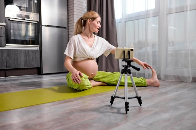 Ładna blondynka kaukaska kobieta w ciąży robi ćwiczenia jogi, oglądając wideo online