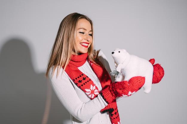 Ładna blondynka kaukaska kobieta w rękawice z jednym palcem i szalik i biały sweter gospodarstwa ładny biały niedźwiedź zabawka i uśmiechnięty.