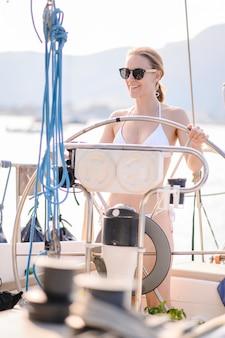 Ładna blondynka ma na sobie strój kąpielowy moda robi letnią podróż na jachcie.