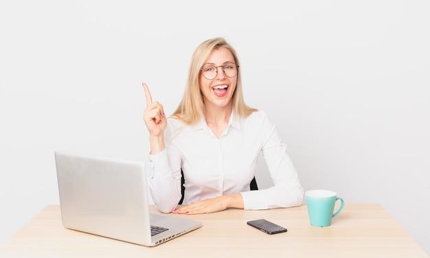 Ładna blondynka młoda blondynka czuje się jak szczęśliwy i podekscytowany geniusz po zrealizowaniu pomysłu i pracy z laptopem
