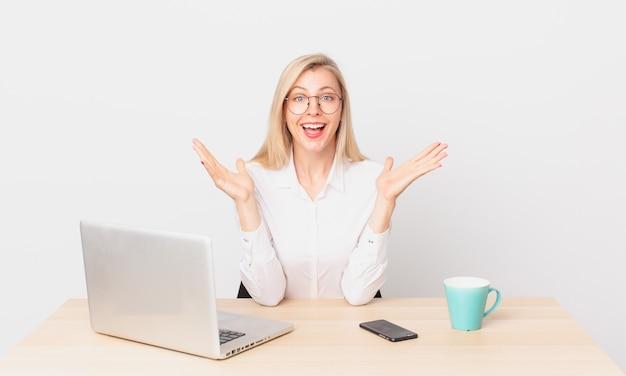 Ładna blondynka młoda blondynka czuje się szczęśliwa i zdumiona czymś niewiarygodnym podczas pracy z laptopem