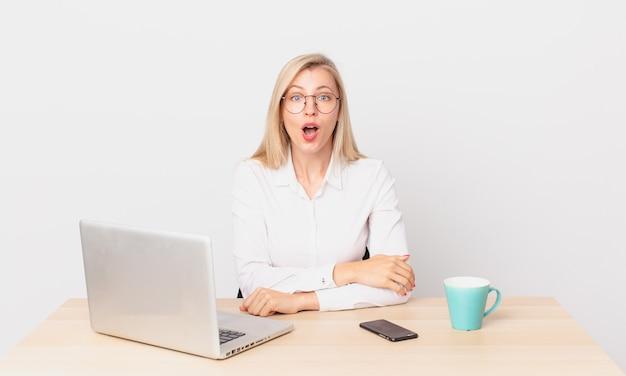 Ładna blondynka młoda blondynka wygląda na bardzo zszokowaną lub zaskoczoną i pracuje z laptopem