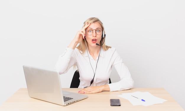 Ładna blondynka młoda blondynka wygląda na szczęśliwą, zdumioną i zdziwioną i pracuje z laptopem
