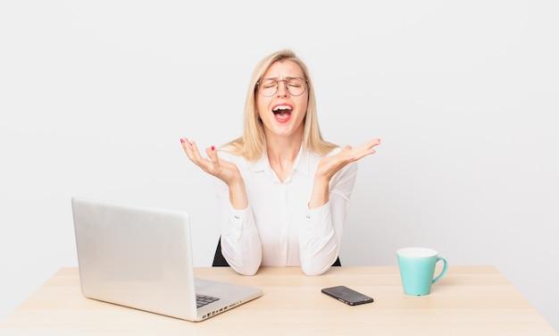 Ładna blondynka młoda blondynka wygląda na zdesperowaną, sfrustrowaną i zestresowaną i pracuje z laptopem