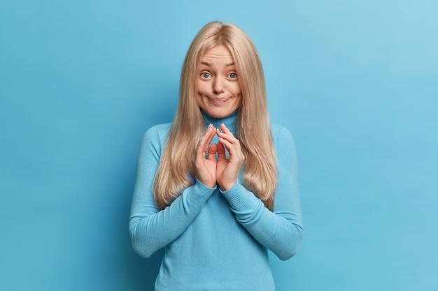 Ładna blondynka młoda europejka ze spiętymi palcami, planuje coś zrobić