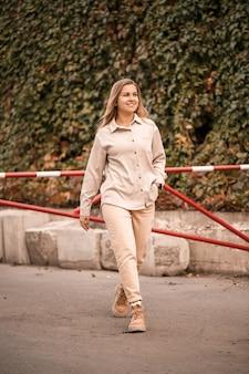 Ładna blondynka, młoda kobieta idzie ulicą, ma na sobie dżinsy i beżową koszulę. piękna dziewczyna ubrana w stylu casual z uśmiechem na twarzy na spacer