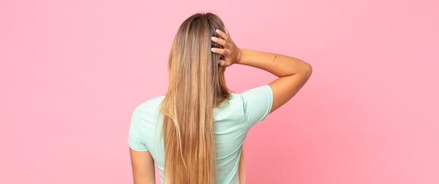 Ładna blondynka myśli lub wątpi, drapie się po głowie, czuje się zdezorientowana i zdezorientowana, widok z tyłu lub z tyłu