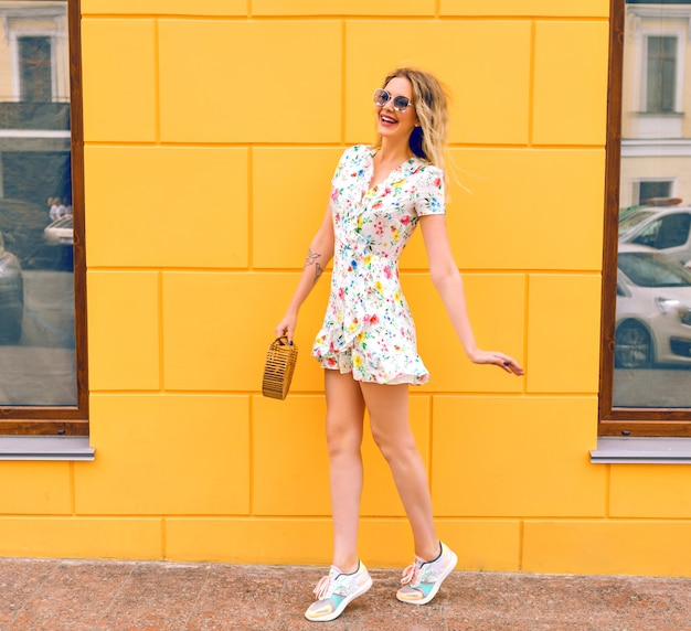 Ładna blondynka na sobie sukienkę w kwiaty, pozowanie w pobliżu żółtej ściany