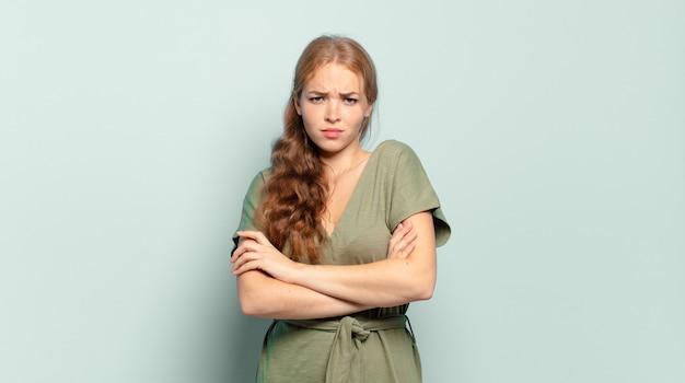Ładna blondynka niezadowolona i rozczarowana, wyglądająca poważnie, zirytowana i wściekła ze skrzyżowanymi rękami