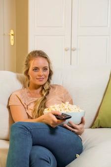 Ładna blondynka ogląda telewizję i je kukurydzę kukurydzianą, siedząc na kanapie