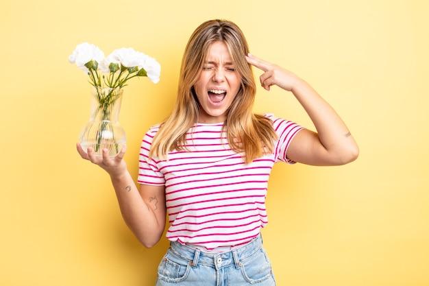 Ładna blondynka patrząc niezadowolony i zestresowany, gest samobójczy dokonywanie znak pistolet. koncepcja dekoracyjnych kwiatów