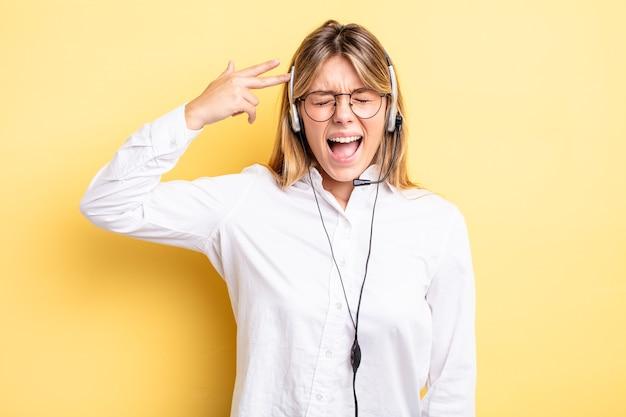 Ładna blondynka patrząc niezadowolony i zestresowany, gest samobójczy dokonywanie znak pistolet. koncepcja zestawu słuchawkowego