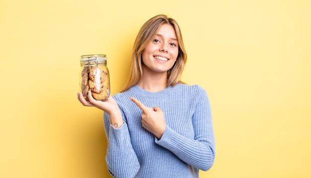 Ładna blondynka patrząc podekscytowany i zaskoczony, wskazując na bok. koncepcja domowych ciasteczek