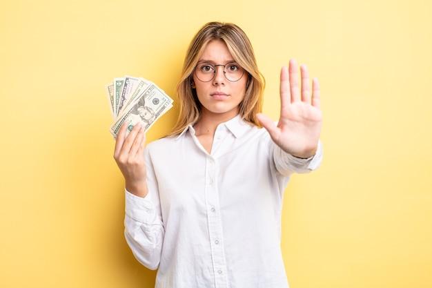 Ładna blondynka patrząc poważne wyświetlono otwartej dłoni, co gest stop. koncepcja banknotów dolarowych