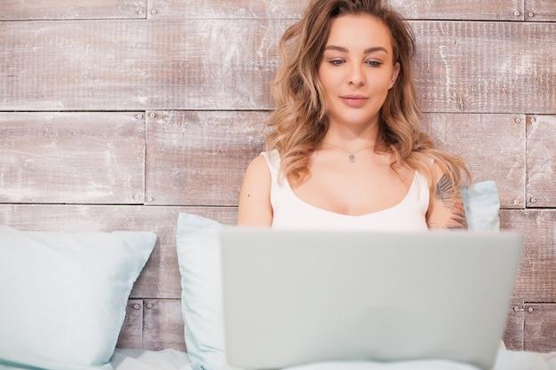 Ładna blondynka pracuje późno w nocy na swoim laptopie w piżamie.