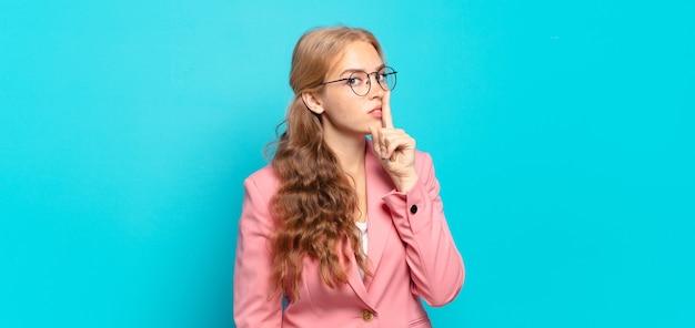 Ładna blondynka prosi o ciszę i spokój, macha palcem przed ustami, mówi cii lub zachowuje tajemnicę