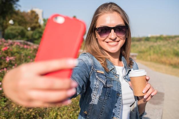 Ładna blondynka robi selfie przy filiżance kawy