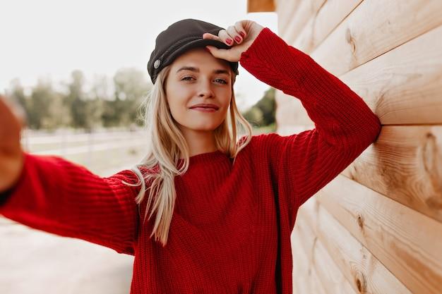 Ładna blondynka robi selfie w pobliżu drewnianego. atrakcyjna kobieta w modnych czerwonych ubraniach.