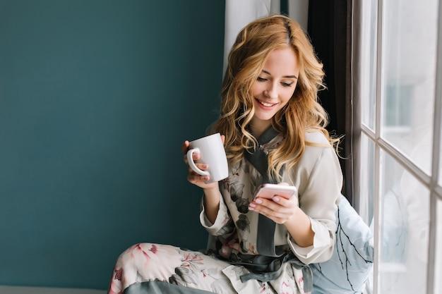 Ładna blondynka siedzi na parapecie z filiżanką kawy, herbaty i smartfona w ręce. ma długie blond falowane włosy, uśmiech i patrzy na telefon. ubrana w piękną jedwabną piżamę.