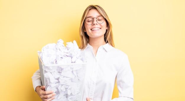 Ładna blondynka śmiejąca się głośno z jakiegoś przezabawnego żartu. koncepcja śmieci z kulkami papierowymi