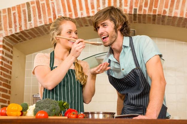 Ładna blondynka sprawia, że jej chłopak smakuje przygotowanie w kuchni