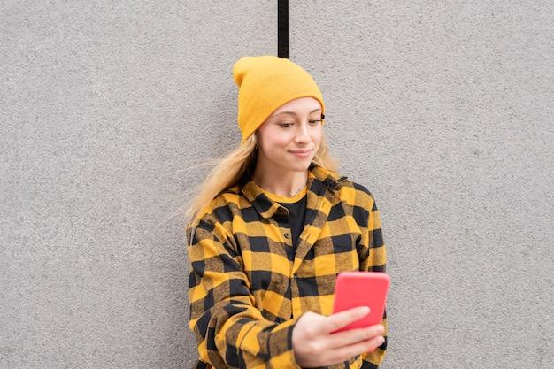 Ładna blondynka, ubrana w zwykłe ubranie, używając swojego smartfona na ulicy