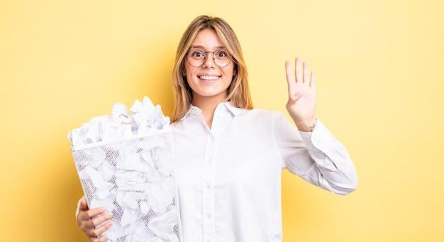 Ładna blondynka uśmiecha się i wygląda przyjaźnie, pokazując numer cztery. koncepcja śmieci z kulkami papierowymi