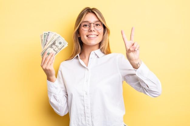 Ładna blondynka uśmiecha się i wygląda przyjaźnie, pokazując numer dwa. koncepcja banknotów dolarowych