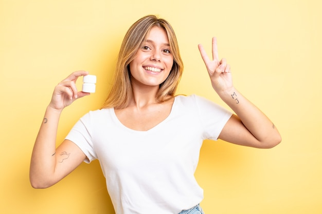Ładna blondynka uśmiecha się i wygląda przyjaźnie, pokazując numer dwa. koncepcja butelki pigułek