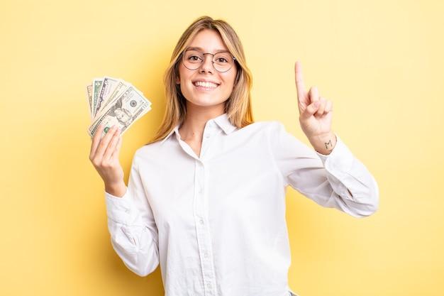 Ładna blondynka uśmiecha się i wygląda przyjaźnie, pokazując numer jeden. koncepcja banknotów dolarowych