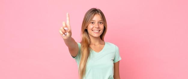 Ładna blondynka uśmiecha się i wygląda przyjaźnie, pokazując numer jeden lub pierwszy z ręką do przodu, odliczając w dół