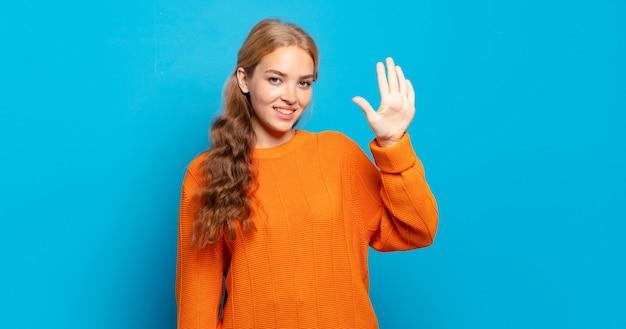Ładna blondynka uśmiecha się i wygląda przyjaźnie, pokazując numer pięć lub piąty z ręką do przodu, odliczając w dół