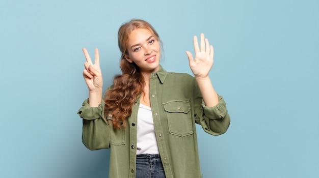 Ładna blondynka uśmiecha się i wygląda przyjaźnie, pokazując numer siedem lub siódmy z ręką do przodu, odliczając w dół