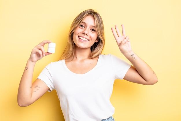 Ładna blondynka uśmiecha się i wygląda przyjaźnie, pokazując numer trzy. koncepcja butelki pigułek