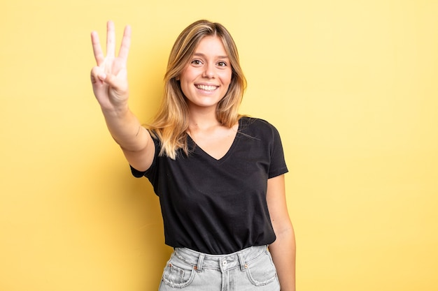 Ładna blondynka uśmiecha się i wygląda przyjaźnie, pokazując numer trzy lub trzeci z ręką do przodu, odliczając w dół