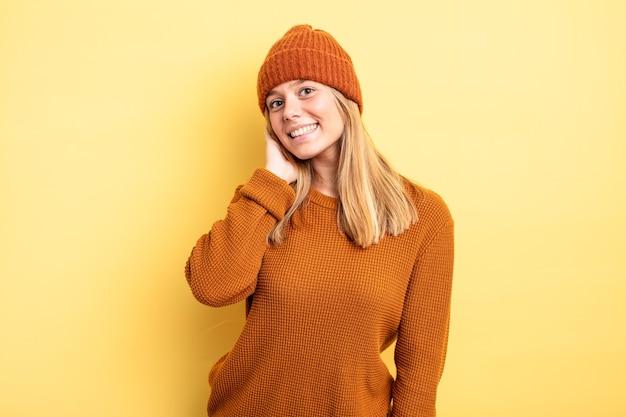 Ładna blondynka uśmiecha się radośnie i od niechcenia, biorąc rękę w głowę z pozytywnym, szczęśliwym i pewnym siebie spojrzeniem
