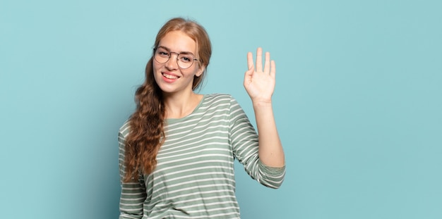 Ładna blondynka uśmiecha się radośnie i wesoło, macha ręką, wita i wita lub żegna się