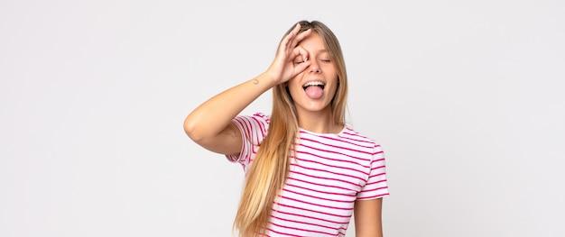 Ładna blondynka uśmiecha się radośnie z śmieszną miną, żartuje i patrzy przez wizjer, szpiegując sekrety