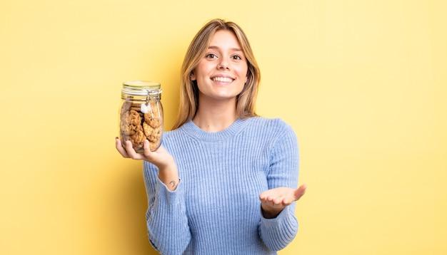 Ładna blondynka uśmiecha się szczęśliwie z przyjazną i oferującą i pokazując koncepcję. koncepcja domowych ciasteczek