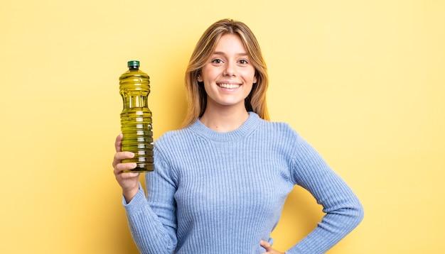Ładna blondynka uśmiecha się szczęśliwie z ręką na biodrze i pewny siebie. koncepcja oliwy z oliwek
