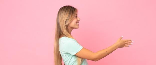 Ładna blondynka uśmiecha się, wita cię i oferuje uścisk dłoni, aby zamknąć udaną transakcję, koncepcja współpracy