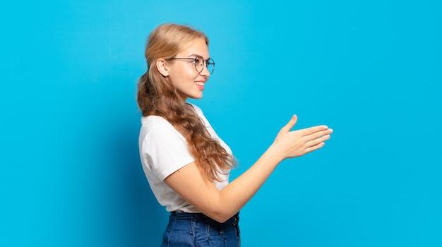Ładna blondynka uśmiecha się, wita i oferuje uścisk dłoni, aby sfinalizować udaną transakcję