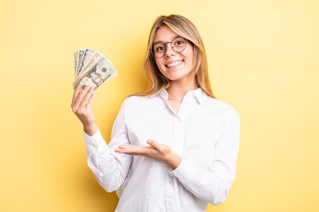Ładna blondynka uśmiechając się radośnie, czując się szczęśliwa i pokazując koncepcję. koncepcja banknotów dolarowych